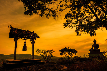 Buddha statue and bell at sunset in Saraburi, Thailand Imagens