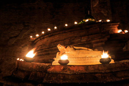 Reclining Golden Buddha, surrounded by candlelight in Thailand