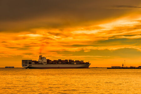 cargo container ship at mediterranean coast in sunset