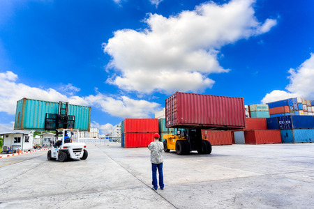 Forklift handling the container box with blue sky