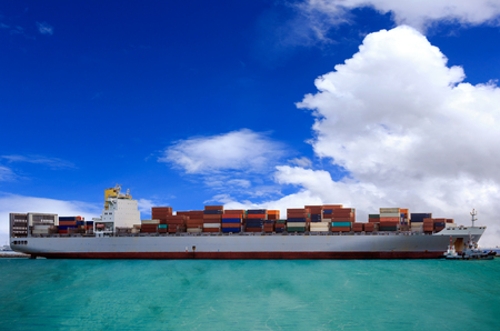 Cargo container ship at mediterranean coast with Blue sky Imagens