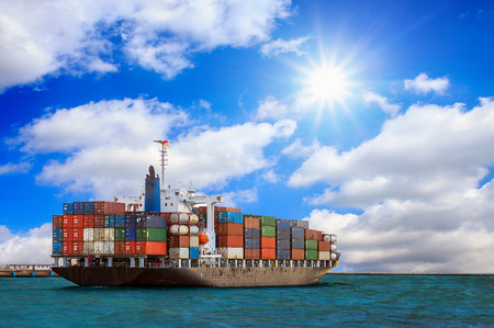 Cargo container ship at mediterranean coast with Blue sky Stockfoto