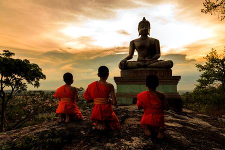 Boeddhabeeld en Novice bij zonsondergang in Saraburi, Thailand