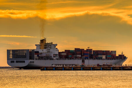 Cargo container ship at mediterranean coast in sunset  Imagens