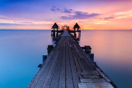 Wood bridge at sunset light in sea Imagens