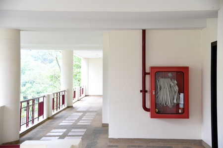 Fire extinguisher and fire hose reel in hotel corridor. Fire hoses rack for use.