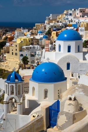 cycladic: Veduta del villaggio di Oia nell'isola di Santorini, in Grecia. Tipici chiese Cicladi in primo piano.