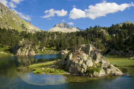 islet: Lake with a small islet in the Aran Valley, Catalan Pyrenees  Stock Photo