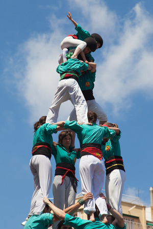 piramide humana: BARCELONA, ESPA�A - 04 de mayo Castellers de la Sagrada Familia formando una pir�mide humana durante la Fiesta Mayor de la Sagrada Familia el 4 de mayo de 2014 en Barcelona, ??Espa�a