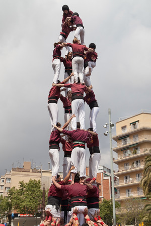 human pyramid: Barcelona Spain  April 19 2015: Xics de Granollers forming a human pyramid during the Festa Major de la Sagrada Familia on April 19 2015 in Barcelona Spain.
