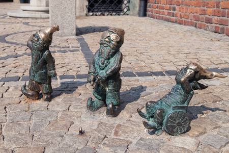 dwarves: Wroclaw, Poland - August 9, 2015: Disabled dwarves on the Market Square of Wroclaw, Poland. Considered a tourist attraction, there are over 300 figurines of dwarves spread all over the city since 2001. Editorial