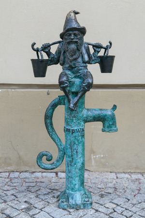 dwarves: Wroclaw, Poland - August 11, 2015: Water-keeper dwarf at the Market Square of Wroclaw, Poland. Considered a tourist attraction, there are over 300 figurines of dwarves spread all over the city since 2001.