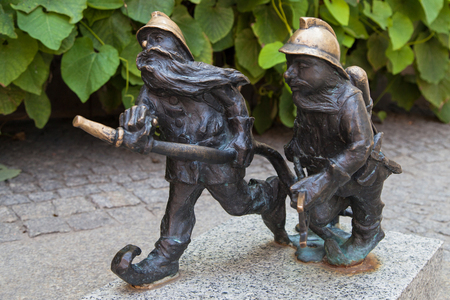 dwarves: Wroclaw, Poland - August 10, 2015: Firemen dwarves on sw Mikolaja street, Wroclaw, Poland. Considered a tourist attraction, there are over 300 figurines of dwarves spread all over the city since 2001.