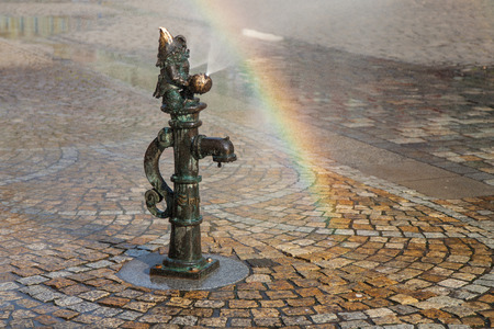 tourist attraction: Wroclaw, Poland - August 11, 2015: Dwarf on a fountain in Rynek Wroclaw, Poland. Considered a tourist attraction, there are over 300 figurines of dwarves spread all over the city since 2001. Stock Photo