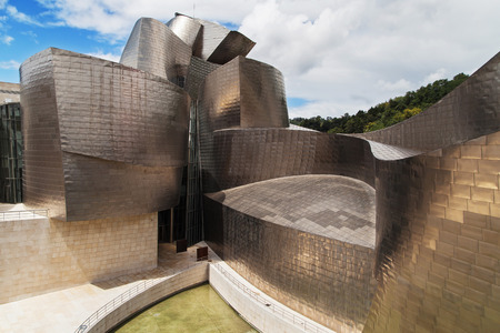 frank   gehry: Bilbao, Spain - August 13, 2014: The Guggenheim museum in Bilbao, Spain. Designed by Frank Gehry in 1997 and built alongside the river Nervion, houses collections of contemporary art.