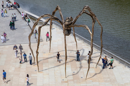 bourgeois: Bilbao, Spain - August 13, 2014: Spider sculpture, created by Louise Bourgeois in 1999, between the Guggenheim museum and the Nervion river, Bilbao, Spain.