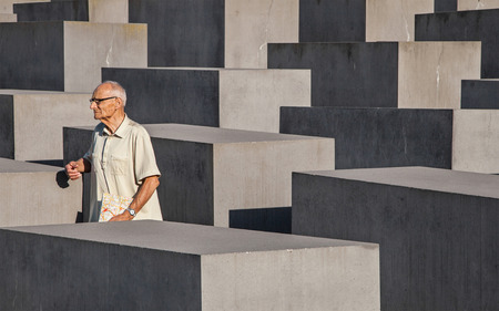 murdered: Berlin, Germany - August 5, 2015: Visitor passing through the blocks of the Memorial to the Murdered Jews of Europe in Berlin, Germany, inaugurated on 2005, sixty years after the end of World War II. Editorial