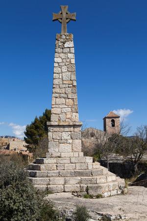 memorial cross: Memorial de la Cruz y la iglesia de Santa María en Siurana, Tarragona, Cataluña, España.