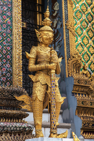 Golden Yaksha guarding the entrance of the Phra Mondop at Wat Phra Kaew, Bangkok, Thailand. Фото со стока