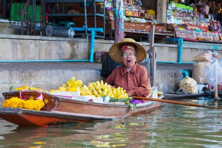 Damnoen Saduak, Thailand - August 29, 2018: Woman selling baby bananas from a boat in Damnoen Saduak Floating Market, Ratchaburi, Thailand.