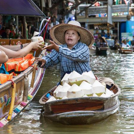 Damnoen Saduak, Thailand - August 29, 2018: Woman selling coconuts from a boat in Damnoen Saduak Floating Market, Ratchaburi, Thailand.