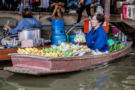 Damnoen Saduak, Thailand - August 29, 2018: Woman selling fruits from a boat in Damnoen Saduak Floating Market, Ratchaburi, Thailand. Editorial