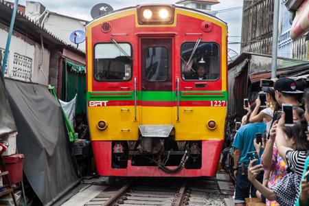 Maeklong, Thailand - August 29, 2018: Train crossing the Umbrella Pull Down Market on August 29, 2018 in Maeklong, Samut Songkhram, Thailand.