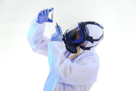 coronavirus epidemic and infectious diseases conceptmale lab technician doing research in the lab with protective suit and gas mask. Stock Photo