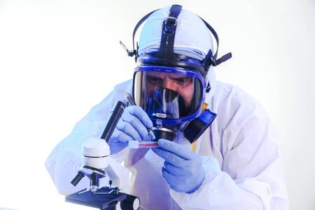 coronavirus epidemic and infectious diseases conceptmale lab technician doing research in the lab with protective suit and gas mask.