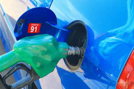 blue car at gas station being filled with fuel