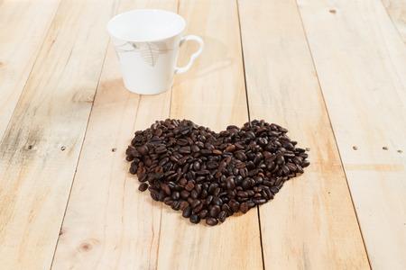 hart: Coffee beans on wooden tale hart shape Stock Photo