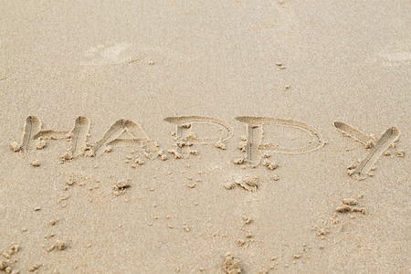 the word Happy in sand on the beach photo