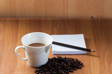 Coffee cup notebook and coffee bean on the wooden table photo