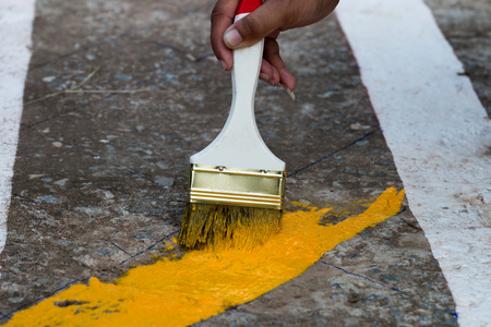 infra construction: painting the the yellow line on the concrete road