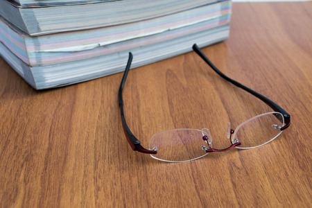 Reading glasses on the wood table photo
