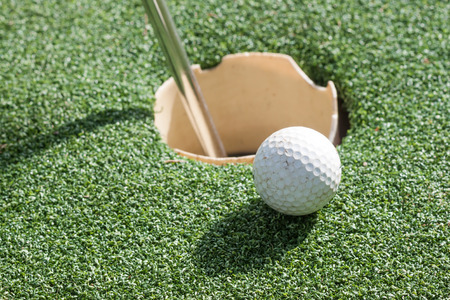 Golf ball on green grass in front of hole photo