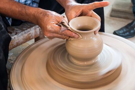 clay pot: Potter hands making in clay on pottery wheel. Potter makes a pottery on the pottery wheel clay pot.