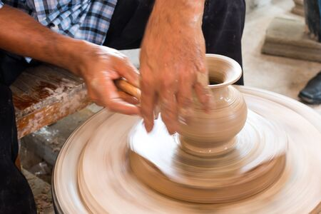 alfarero: Potter hands making in clay on pottery wheel. Potter makes a pottery on the pottery wheel clay pot.