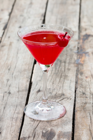 Cherry cocktail in martini glass on rustic table Imagens