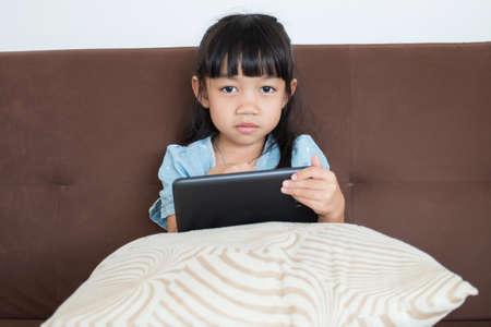 engrossed: Portrait of a young child in a home interior engrossed in a game on a digital tablet