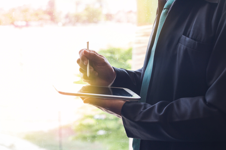 Businessman using tablet computer. Businessman write on notepad
