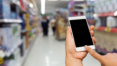 doing business: Hand using smart phone for doing business or banking or buying online on blur shopping mall background.