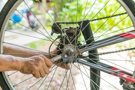 close-up of mechanic setting up chain on bicycle in workshop