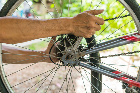 close-up of mechanic setting up chain on bicycle in workshop Imagens - 81915817