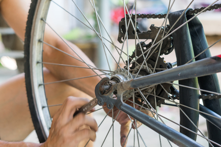 close-up of mechanic setting up chain on bicycle in workshop Imagens - 82159953
