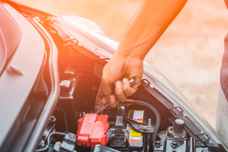 Hand of auto mechanic repair car battery in car repair shop