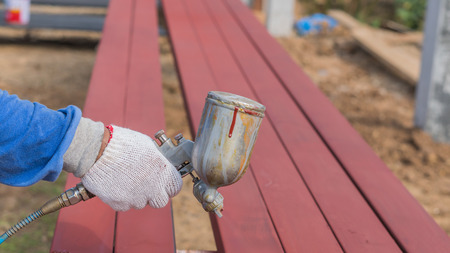 hand holding spray gun and painted steel Stock Photo