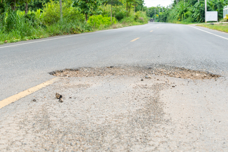 dangerous  hole in the asphalt road