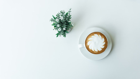 White cup of hot Latte art coffee with Flower Pot on white table Imagens