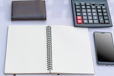 blank notepad and wallet with smart phone and calculator on work table